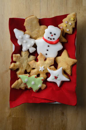 home baked: Overhead shot of a variety of plain and iced (frosted) home baked Christmas biscuits (cookies)  in a rectangular white dish with red napkins on wooden table. Stock Photo