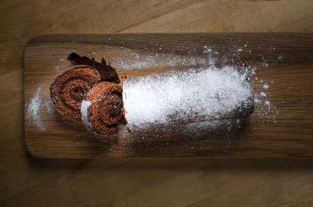 rebanada de pastel: Tiro de arriba de una longitud total de chocolate de Navidad Tronco de Navidad o de la torta del rodillo suizo, en la tabla larga paleta de madera, espolvoreado con azúcar en polvo blanco.