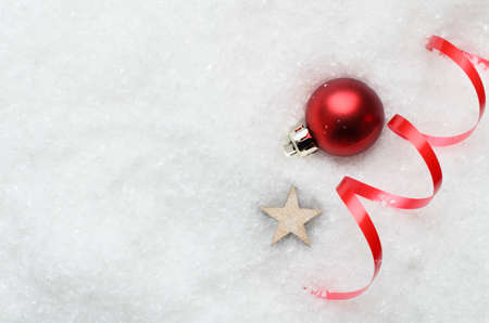 partially: Overhead of Christmas background with decorative red bauble, ribbon swirl and wooden star partially buried in artificial white snow on the right. Copy space to the left.