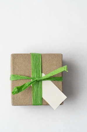 understated: Overhead shot of a simple brown gift box, with green raffia ribbon and blank label on white background.