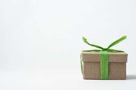 Eye level shot of simple brown gift box in lower right of frame with closed lid, tied with light green raffia ribbon on off white background.