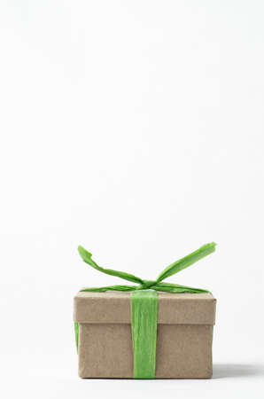 understated: Simple brown gift box with lid, tied to a top knot with light green raffia ribbon. Stock Photo