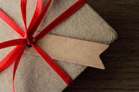 generosidad: Overhead de cerca de una etiqueta en blanco atado a una caja de regalo de color marrón claro con la cinta roja en la superficie de madera de roble.