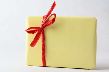 no label: A gift package, very simply wrapped in plain yellow paper with red raffia ribbon tied to a bow.  No label. Copy space on wrapping and background.