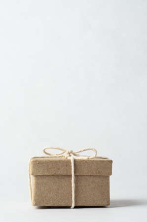 surprise box: Simple brown box with closed lid, tied to a bow with string, signifying a gift, surprise or secret.