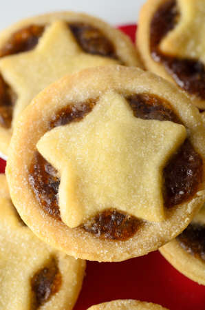 Overhead close up of a stack of Christmas mince pies with star shaped pastry toppers and filling exposed.  Red napkin and white plate below. Stock Photo