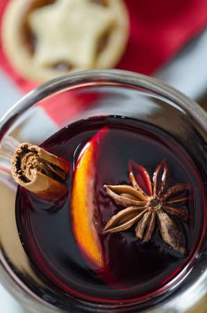 glass topped: Overhead close up of a glass of spicy mulled wine with star topped Christmas mince pie on red napkin in soft focus background. Stock Photo