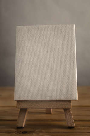 portrait orientation: A textured white blank art canvas, in portrait or vertical orientation, resting on an easel on a wood planked floor.  Retro hues.