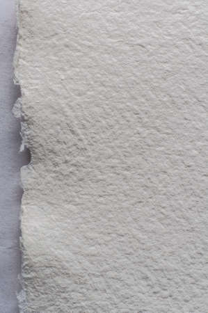 uneven edge: A white piece of textured artists watercolour paper, with torn edge. Stock Photo