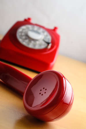 earpiece: Angled shot of a 60s to 70s retro red British telephone, with close up of receivers earpiece in foreground and base in soft focus background. Stock Photo