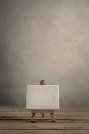 blank art canvas on easel standing on wood plank floor empty