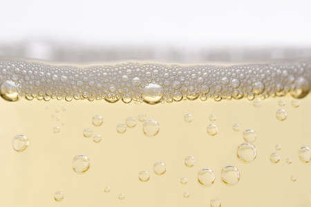 bubble level: Close up (macro) of  champagne glass, filled with sparkling white wine.  Rising bubbles topped by layer of froth. Eye level shot. Stock Photo