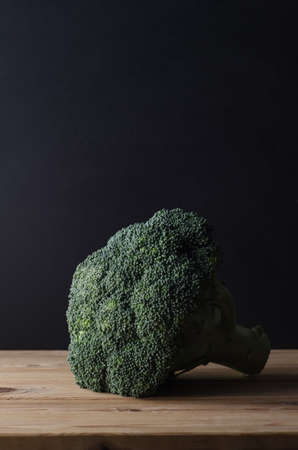 intact: A head of dark green broccoli with stalk intact, on wooden planked table against black chalkboard background.  Moody lighting. Stock Photo