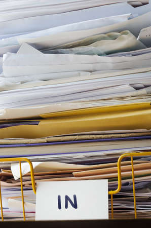 A wire office tray labeled In, piled high with papers, documents and folders that reach to the top of the frame and extending beyond it. Stock Photo
