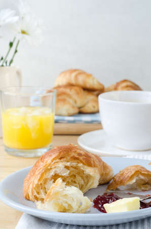 Continental Breakfast table setting laid with croissants, orange juice, coffee and flowers. A serving of partly eaten croissant with butter and jam is in the foreground. Stock Photo
