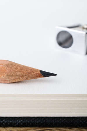 Close up of the tip of a wooden graphite drawing pencil on the edge of a blank sketch book page with sharpener in soft focus background.