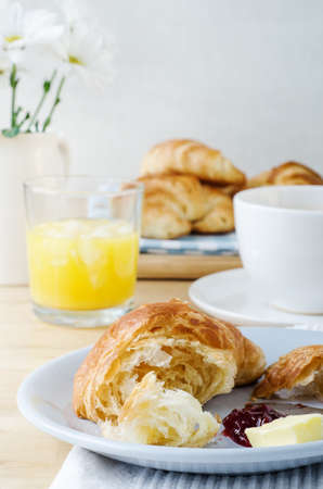 smeared: Continental Breakfast table setting laid with croissants, orange juice, coffee and flowers. A serving of partly eaten croissant with butter and jam is in the foreground. Stock Photo