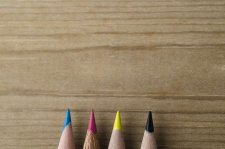 Tips of four pencils, pointing upwards into copy space of wooden background, representing the CMYK model of colour printing.