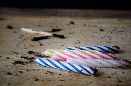 Used birthday candles and matches, burned and blackened. Left scattered on a wooden chopping board with cake crumbs as remnants at the end of party celebrations.