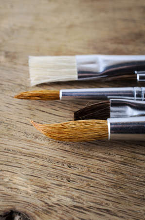 A row of clean, unused paintbrushes with a mixture of bristle types, lying on an oak wood table. Close up shot, just above eye level.