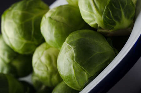 Close up of leafy green brussel sprouts in white enamel baking pan with navy blue stripe. Stock Photo