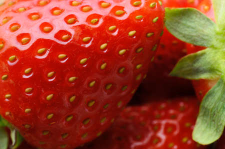 Close up (macro) of fresh red strawberries showing texture, partial outline and leaves.