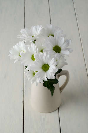 A small bunch of white flowers chrysanthemums with green leaf a small bunch of white flowers chrysanthemums with green leaf in a beige jug mightylinksfo