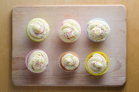 domesticity: Overhead view of six decoratively iced and sprinkled cupcakes in colourful silicone and plain paper cases. Placed on wooden chopping board with table beneath. Stock Photo