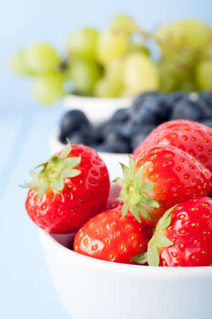 A variety of fresh fruits in white ceramic bowls on pale blue table and background. Red strawberries in foreground with blueberries and green grapes in soft focus background.