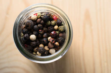 Overhead close up shot of mixed peppercorns in a glass container on a light wood table with copy space to the right.