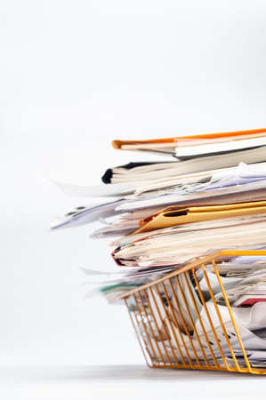 untidy: Angled shot of a yellow wire office filing or in tray, stacked high with a messy pile of documents. Copy space on white background to left and above. Stock Photo
