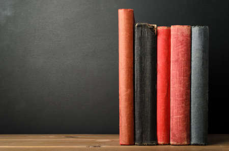 A row of upright books with blank spines at eye level on wood planked desk with black chalkboard background; providing copy space to left. Stok Fotoğraf
