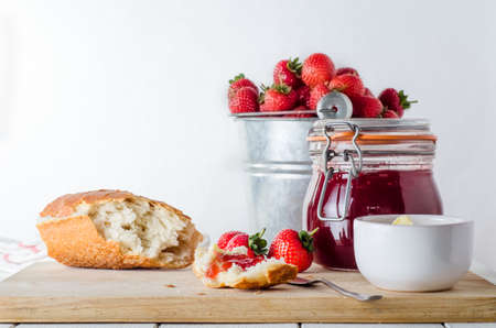 A kitchen table scene of freshly made strawberry jam in storage jar with a tin pail of strawberries in the background; bread, butter and strawberries on a wooden chopping board. Stock Photo