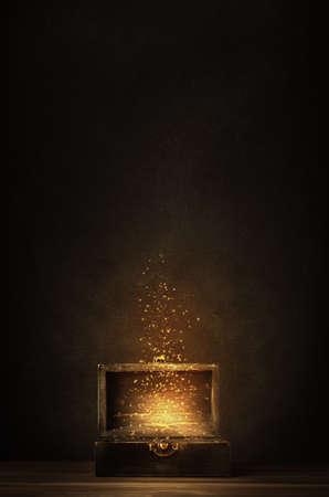 Glühende goldene Funkeln und Sterne steigen aus einer alten, geöffneten hölzernen Schatzkiste. Dunkel beleuchtet auf einer planked Oberfläche mit schwarzem Tafelhintergrund. Standard-Bild