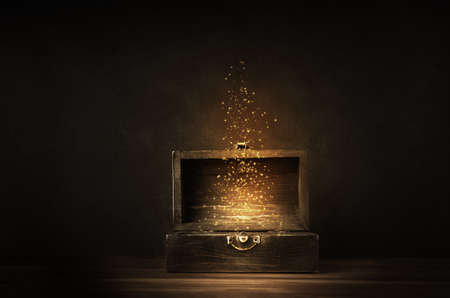 Glühende goldene Funkeln und Sterne steigen aus einer alten, geöffneten hölzernen Schatzkiste. Dunkel beleuchtet auf einer planked Oberfläche mit schwarzem Tafelhintergrund.
