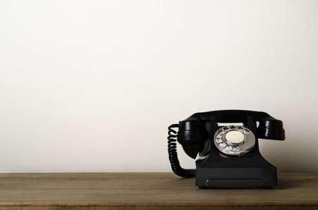 Noir, téléphone en bakélite d'époque des années 1940 au niveau des yeux sur un bureau en bois avec un mur blanc ivoire à l'arrière-plan offrant un espace de copie à gauche. Banque d'images - 89441027