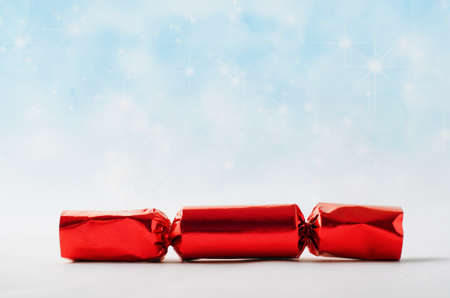 A single, red foil Christmas cracker, against light blue bokeh background simulating a star filled sky with falling snow.
