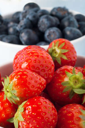 Close up of strawberries filling a white ceramic bowl with blueberries in soft focus background.