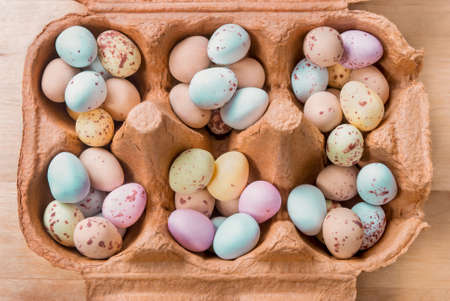 Overhead view of an opened brown egg carton, filled with piles of small egg shaped Easter sweets.