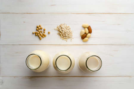 Overhead shot of soya, oat and almond milk drinks in a row of open bottles with ingredients on painted white, wood planked table. Shallow depth of field.