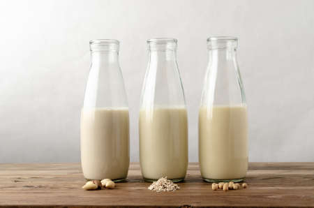 Row of three glass bottles containing dairy free milk substitute drinks. Key ingredients of almonds; oats and soya beans in foreground on wood planked table.