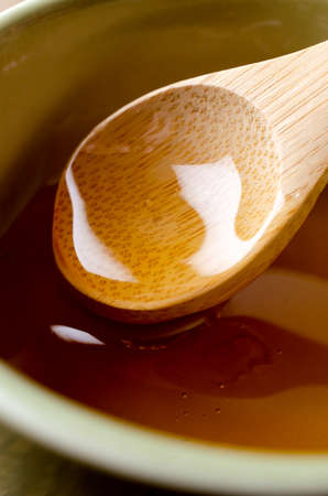 Close up of wooden spoon lifting clear golden honey from green ceramic bowl.