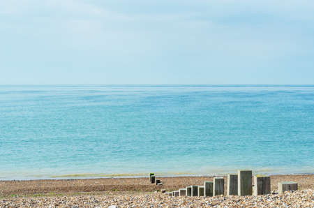 Pebble beach scene of calm sea on bright day. Wooden posts of varying heights lead towards the shoreline.