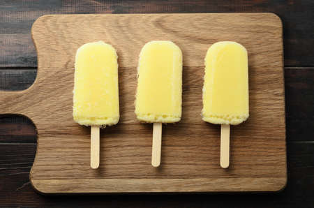 Overhead shot of three yellow pineapple ice lollies lined in a row on a light wooden chopping board with dark planked table behind.