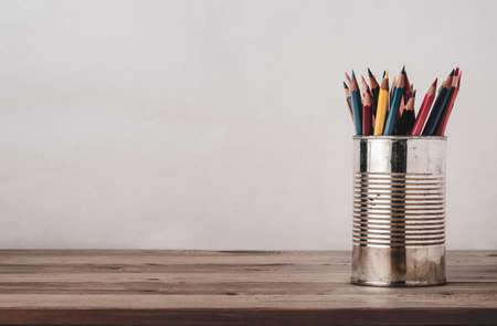 A variety of coloured pencils in an old metal tin on a wood plank desk with copy space to left and above. Filtered for retro effect.