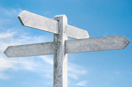 Old weathered wooden signpost against blue sky with four sign choices pointing in different directions. Stock Photo