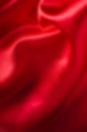 Red satin fabric, draping with soft folds. Blurred background.