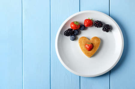Overhead shot of a heart shaped breakfast pancake on a white plate, topped with a cut strawberry. Above it is  an arc of Summer fruits.  Set on a blue painted wood planked table.
