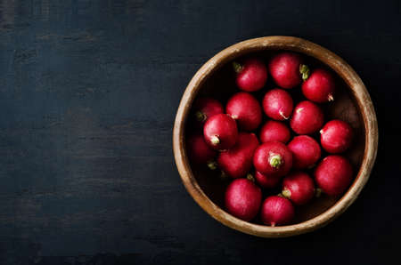 Overhead shot of radishes filling an old wooden bowl on grungy black surface with copy space to the left.