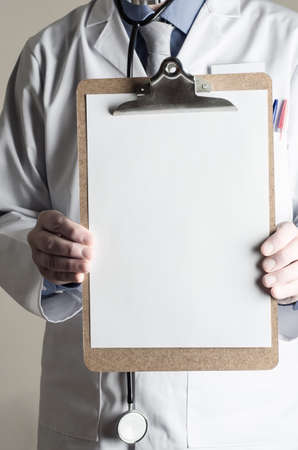 Male model dressed as Doctor. Facing front and holding up a clipboard with blank sheet of paper as a sign providing copy space for a message.